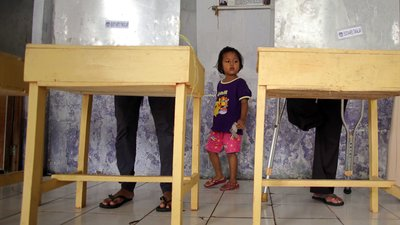 Two voting booths are being used; one by a person with one leg. A young girl looks up at the person voting.