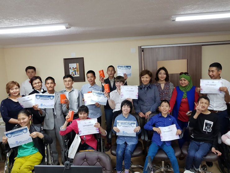 A group of youth participants with different types of disabilities hold up certificates