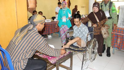 A man dips his a toe on his left foot in indelible ink