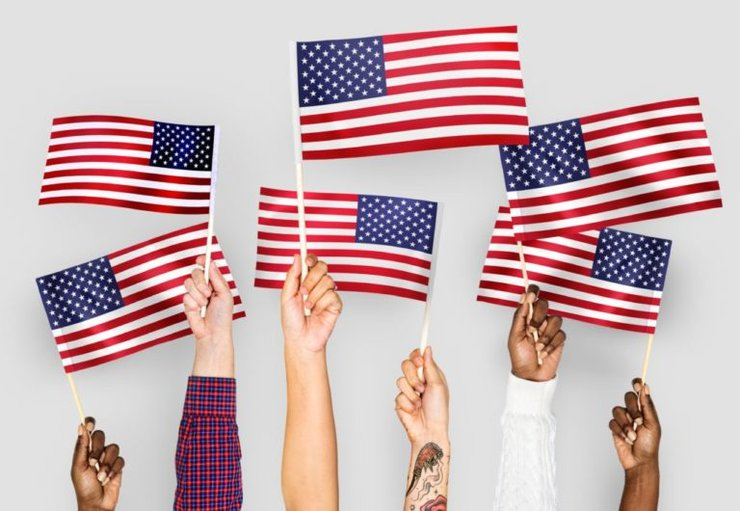 Photo from article showing hands holding American flags.