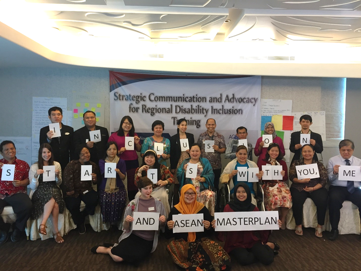 "Participants pose for a group photo and hold signs that read: ""Inclusion starts with you, me and the ASEAN Masterplan."""
