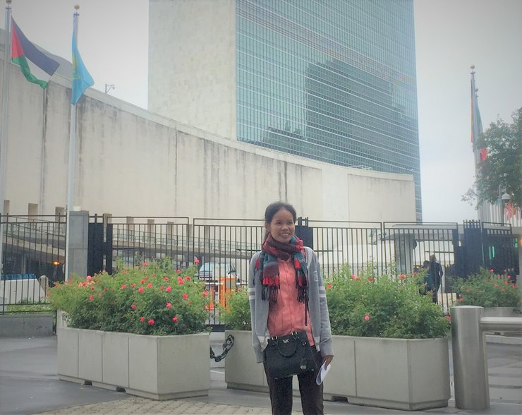 A woman stands in front of the UN building. There are several flags flying