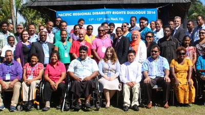 Participants from the Pacific Regional Disability Rights Dialogue in front of a banner