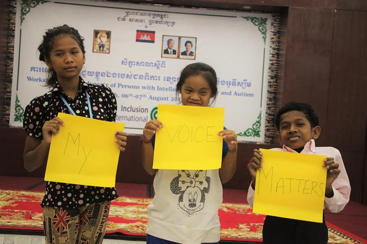 "Three Cambodian children with disabilities hold up signs saying ""My Voice Matters"""
