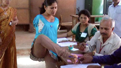 A woman signs in to vote using her foot