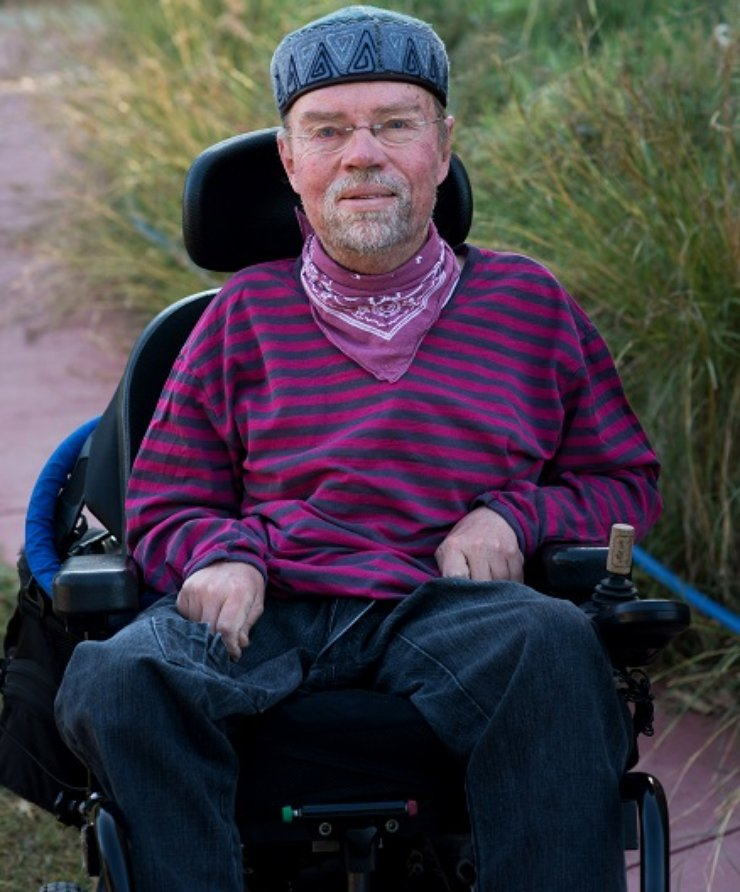 A man using a powerchair has a hat and a beard and smiles at the camera