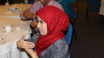 Woman with red headscarf learns a new sign