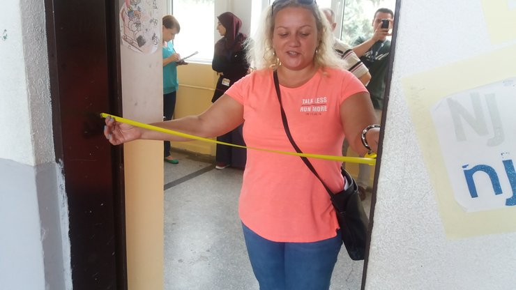 A woman holds a tape measure across a doorway