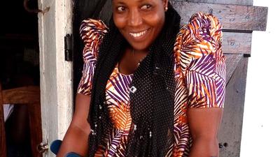 A woman using crutches smiles