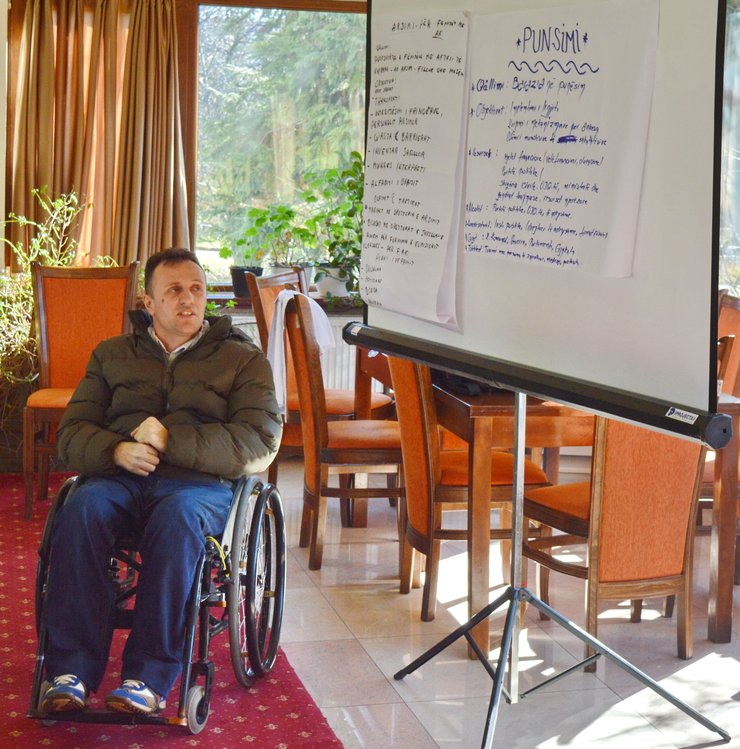 A man using a wheelchair looks up at a presentation board with writing on it.