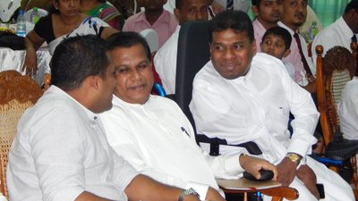 Senarath Attanayake, who is using a wheelchair, speaks with colleagues