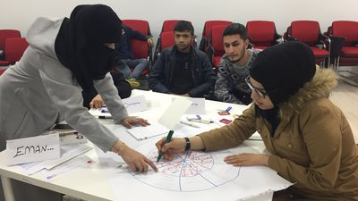 A group of youth draw a chart together