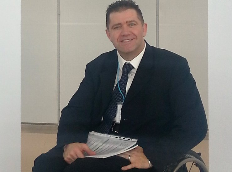 A man using a wheelchair and wearing a suit smiles at the camera