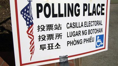 "Sign says ""polling place"" in 7 languages, includes access icon"