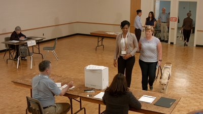 A woman who is blind uses a guide dog and receives support from a poll worker to arrive at the voter registration table