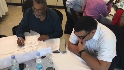 An election commissioner writes on a piece of flip chart paper as IFES Inclusion Advisor watches