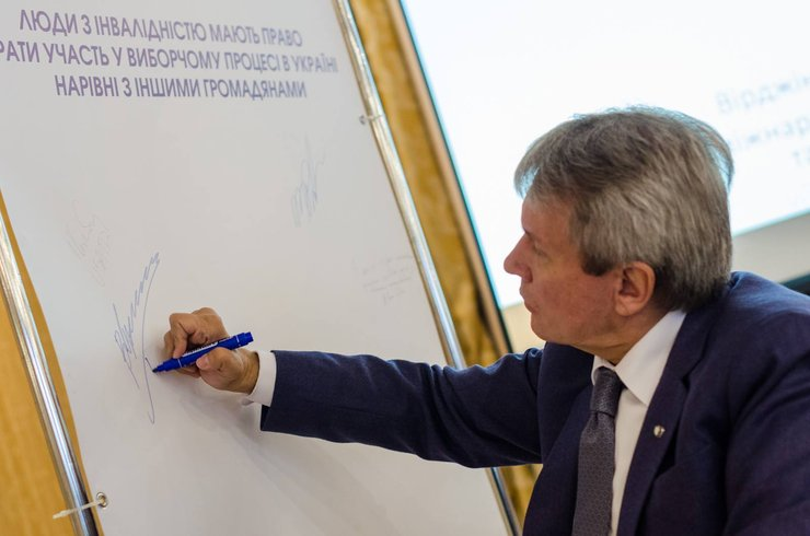 Commissioner Valeriya Sushkeyvych signs a banner supporting participation of persons with disabilities in political life.