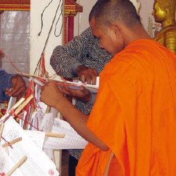 A man wearing bright orange robes looks down at a voter registration list