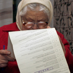 An older woman with glasses looks down at a ballot