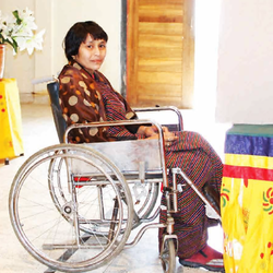 A woman using a wheelchair sits in front of a voting booth