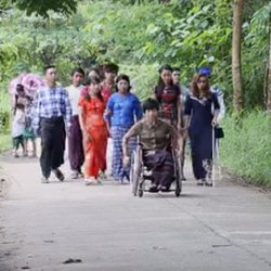 A crowd of people with disabilities walk down a road