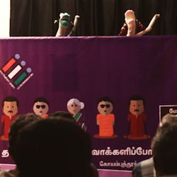 Two sock puppets perform in front of an audience