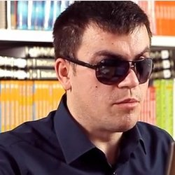 A man sitting in front of a wall of books is wearing dark sunglasses and speaking