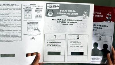 Two hands hold up a braille ballot guide and a ballot
