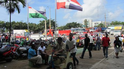 In the foreground is a man hand-peddling a wheelchair. Behind him is a parking lot full of cars and scooters. The Dominican Republic's flag flies against a blue sky.