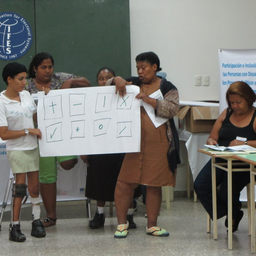 There are four women standing in front of a classroom. At least two of them appear to be using crutches or braces. They are holding up a large poster with eight different squares drawn on it. Each square is marked in a different way, e.g. a plus sign.
