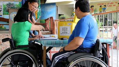 On the left is a woman using a wheelchair. Her face is turned away from the camera and she's talking to two women who are standing; all three are leaning over a table. On the right, in the foreground, is a man using a wheelchair observing the conversation