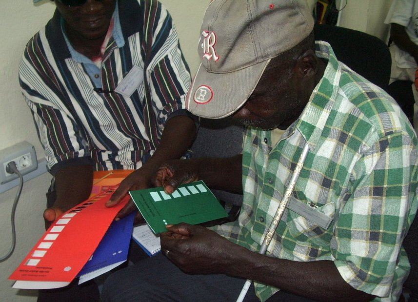 In the foreground, one man appears to have a metal cane and is looking down at a green tactile ballot. The man next to him is holding several documents, including a large red tactile ballot, a blue tactile ballot, and a notepad.