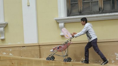 A young man is pushing a pink stroller with a young girl up a wooden ramp outstide of a yellow building.