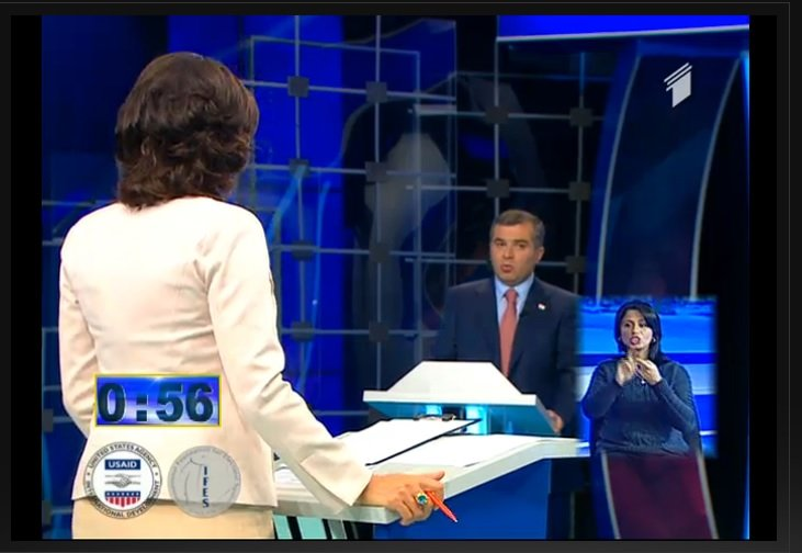 In the front is a woman with her back to the camera. She questions a man opposite her, a political candidate. In the lower right corner of the screen, a woman is interpreting in Georgian sign language.