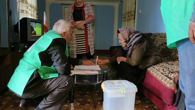 An older woman with a head scarf sits on a couch and leans over a low table to complete her ballot. Opposite the table is a poll worker crouching and pointing to the ballot. Both he and another person are wearing green vests.