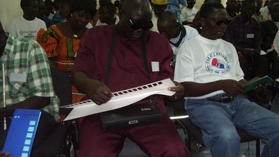 In a large room there are several people sitting in rows. In the front row are three men with visual disabilities. They are holding tactile ballot guides and looking down at them.
