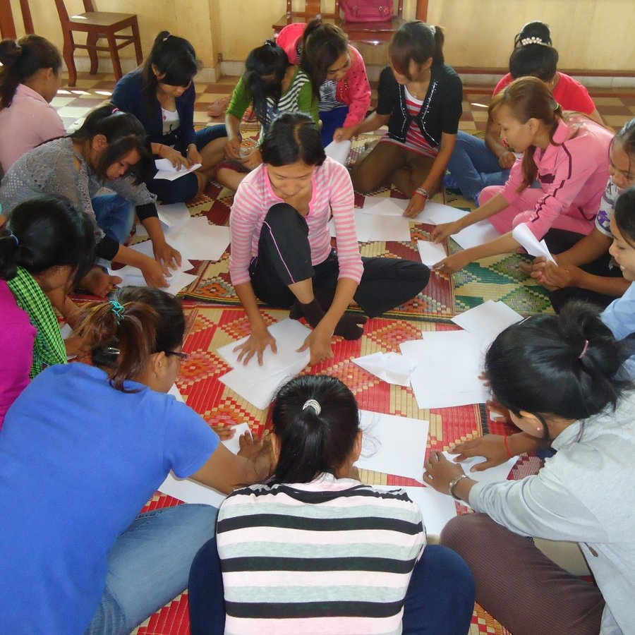 There are several women sitting in a circle inside a house. They appear to be completing worksheets.