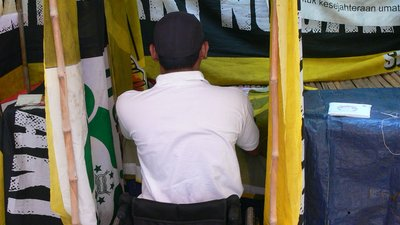A man using a wheelchair is inside a small makeshift tent outdoors. There is a table that is easy for him to access and write on. Behind the table is a curtain made of different fabrics and posters.