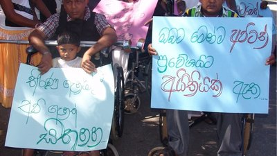 on the left of a crowd is a man using a wheelchair (Senarath) holding up a sign