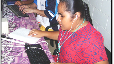 A Samoan woman sits in front of a computer, simultaneously reading braille and listening