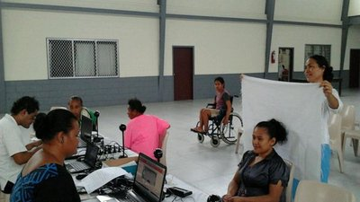 A busy room shows voters registering to vote, including a women using a wheelchair