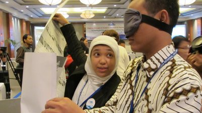 In the foreground, there is a man wearing a blindfold. He is holding a large sheet of paper in his hands (it may be a tactile ballot guide). To his right stands a woman, who is holding up a large ballot with her right hand. She is talking to him
