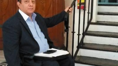 A man in a wheelchair sits at the bottom of a staircase
