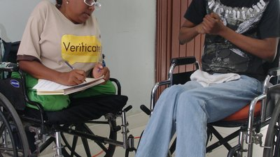 "A woman using a wheelchair writes on a notepad. She wears a brown shirt with ""Verifícate"" written on it, identifying her as a poll worker. She is peering over her glasses at the young man next to her. The man is using a wheelchair and clasps his hands"
