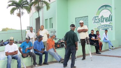 Eight men and two women are sitting or standing near a low wall painted light green. It is apparent that they are waiting in line. At least two men seem to be using crutches.