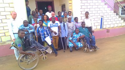 About 20 people stand in front of a building. Two are using wheelchairs, at least four are using canes or crutches, and two appear to have albinism.