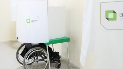 A person using a wheelchair completes their ballot in a private voting booth