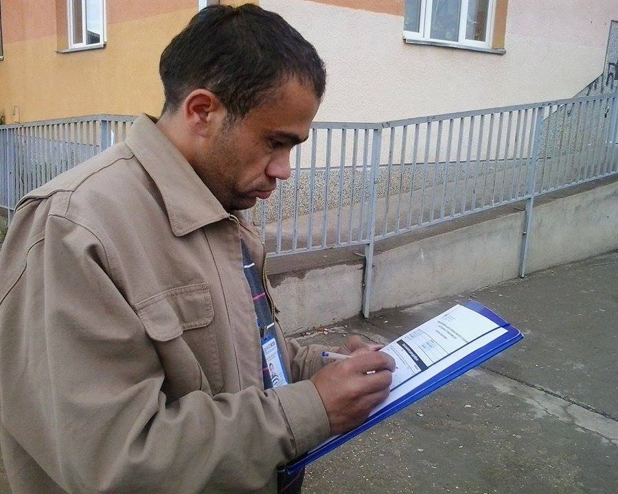 A man is holding a clipboard and looking down at it. He has a pen in his right hand and is making notes. He's wearing a beige, heavy jacket. Behind him is a metal railing and a yellow building.