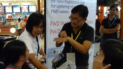 One woman, an election worker, is sitting at a table. The other woman sitting at the table, who is registering to vote, speaks in Filipino Sign Language with an interpreter. A third woman is pressing the voter's thumb onto a portable scanner.