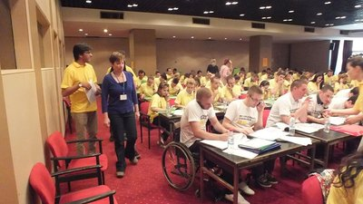 In a large room are several people sitting in rows, wearing yellow or white shirts and speaking into mobile phones. One man in the front row is using a wheelchair.